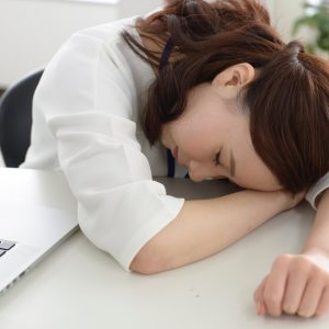机に突っ伏して眠る女性