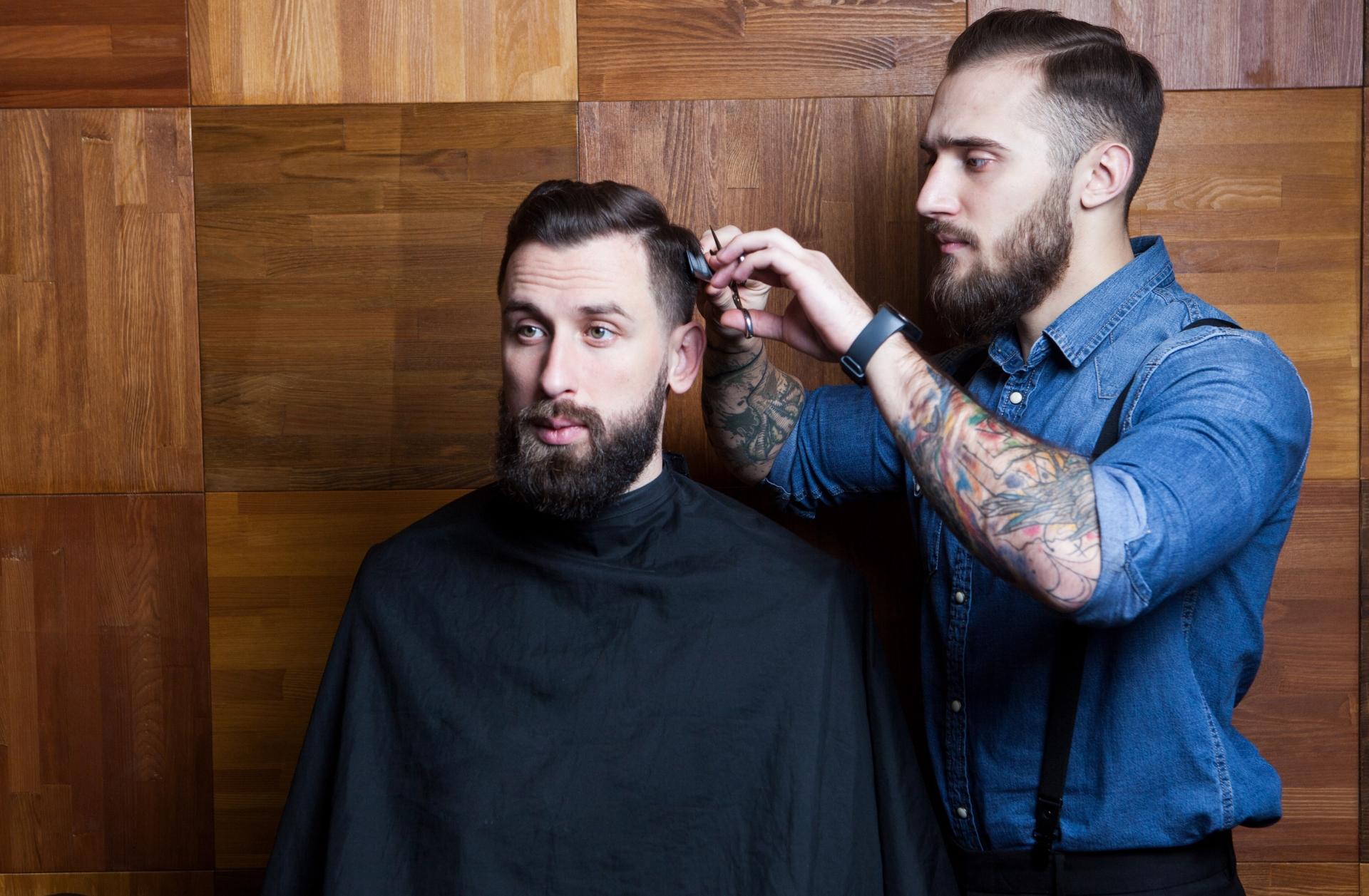 美容師に髪を切られる男性
