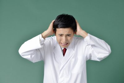 頭を抱えて悩む医師